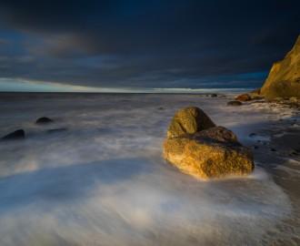 Ostsee bei abendlichen Licht und langer Belichtung,Untergehende Sonne bestrahlt Äste und Steine im Meerwasser,schöne Wolken bei einem Sonnenuntergang, bewegte See mit Gischt am Strand